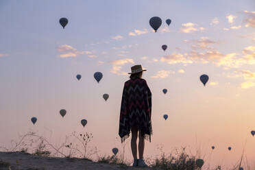 Young woman and hot air balloons in the evening, Goreme, Cappadocia, Turkey - KNTF03301