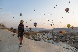 Young woman and hot air balloons in the evening, Goreme, Cappadocia, Turkey - KNTF03304