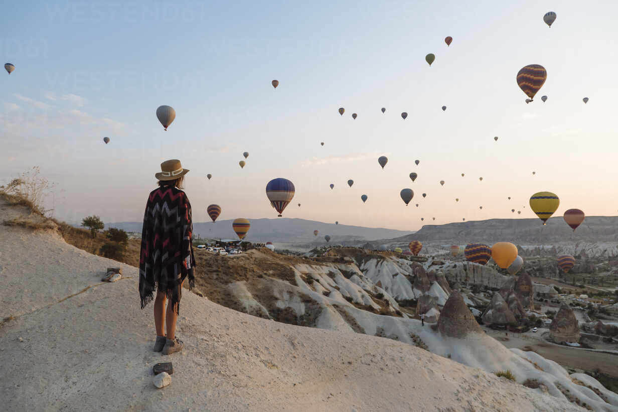 Young woman and hot air balloons in the evening, Goreme, Cappadocia, Turkey - KNTF03304 - Konstantin Trubavin/Westend61