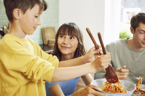 Mother eating spaghetti with her sons in the kitchen - MCF00167