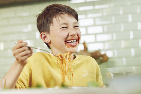 Messy boy eating spaghetti with tomato sauce - MCF00182