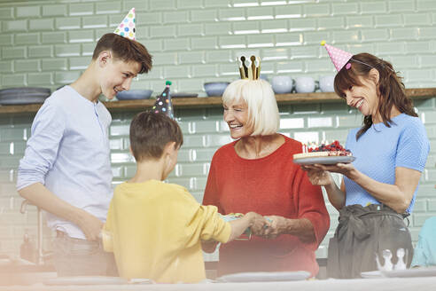 Mother and sons celebrating grandmother's bithday in their kitchen - MCF00203