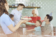 Mother and sons celebrating grandmother's bithday in their kitchen - MCF00206