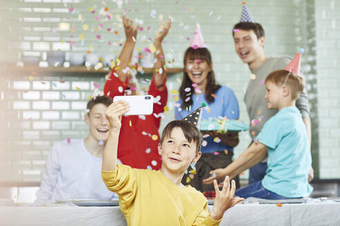 Mother and sons celebrating grandmother's bithday in their kitchen, boy taking selfies - MCF00212