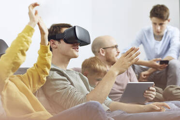 Happy family sitting on couch, using VR goggles and mobile devices - MCF00227