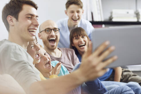 Big familiy having fun at home, using digital tablet - MCF00236
