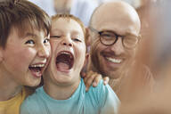 Father and sons having fun at home - MCF00245