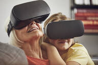 Grandmother using VR glasses with her grandson - MCF00260