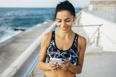 Woman using smartphone and in-ear during workout, sitting on a pier - OYF00022