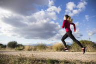 Young woman jogging on road in countryside - ABZF02539