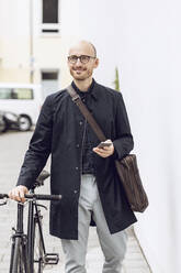 Man with bicycle going to work holding his smartphone - MCF00268