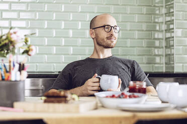 Man holding a cup sitting at the breakfast table at home - MCF00283