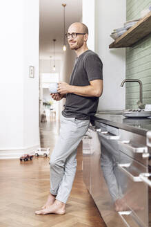 Man with a cup standing in the morning at home in the kitchen - MCF00286