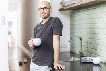 Man with a cup standing in the morning at home in the kitchen - MCF00289