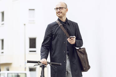 Man with bicycle going to work holding his smartphone - MCF00316