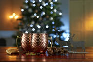 Close-up of mulled wine with food and decorations on table against illuminated Christmas tree at home - KSWF02087