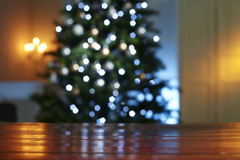 Close-up of wooden table with illuminated Christmas tree in background at home - KSWF02090