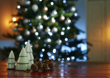 Close-up of small Christmas trees with pine cones on wooden table at home - KSWF02093