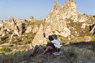 Couple looking to Uchisar castle, Cappadocia, Turkey - KNTF03309