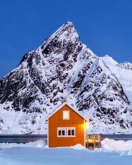 Yellow rorbuer hut in the snow at twilight, Sakrisoy, Moskenesoya, Lofoten Islands, Nordland, Norway, Europe - RHPLF07311