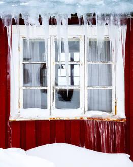 Frozen icicles on a traditional Rorbu window in winter, Nordland, Lofoten Islands, Norway, Europe - RHPLF07320
