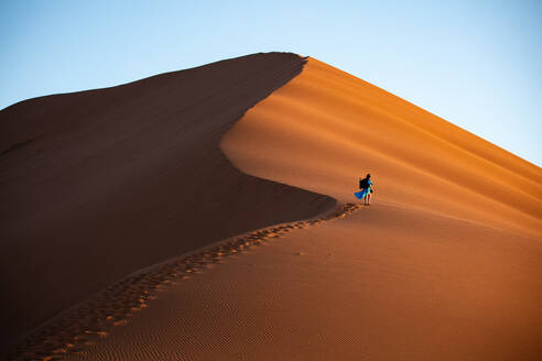 Shot of model Climbing Dune 13 with photography gear, Sossusvlei, Namibia, Africa - RHPLF07380