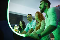 Focused friends playing with a gaming machine in an amusement arcade - ZEDF02568