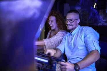 Couple playing and having fun in an amusement arcade - ZEDF02571