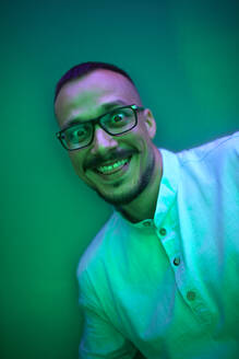 Portrait of man in green light pulling faces - ZEDF02577