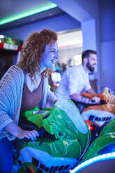 Woman playing and having fun with a driving simulator in an amusement arcade - ZEDF02583