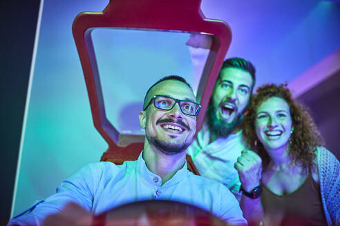 Happy friends playing and having fun with a driving simulator in an amusement arcade - ZEDF02586