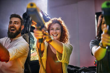Happy friends playing and shooting with pistols in an amusement arcade - ZEDF02592