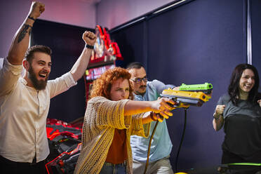 Happy friends playing and shooting with pistols in an amusement arcade - ZEDF02604