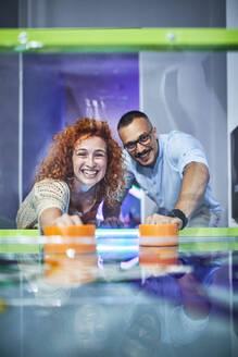 Happy couple playing air hockey and having fun in an amusement arcade - ZEDF02613