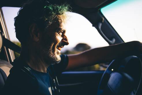 Mature man driving at sunset - OCMF00594