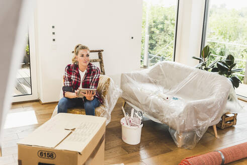Woman moving into new home using tablet - UUF18855
