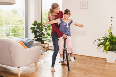 Mother supporting daughter on unicycle at home - UUF18897