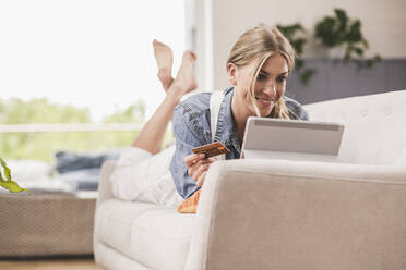 Smiling woman on couch with credit card and tablet - UUF18945