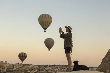 Young woman and hot air ballons, Goreme, Cappadocia, Turkey - KNTF03315