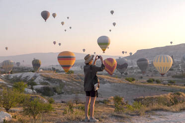Young woman and hot air ballons, Goreme, Cappadocia, Turkey - KNTF03321