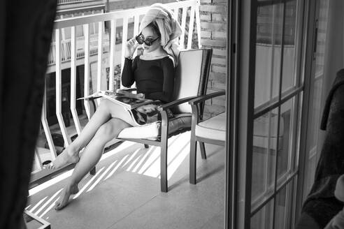 Glamour lady reading a magazine on balcony, hand on glasses - LJF00874