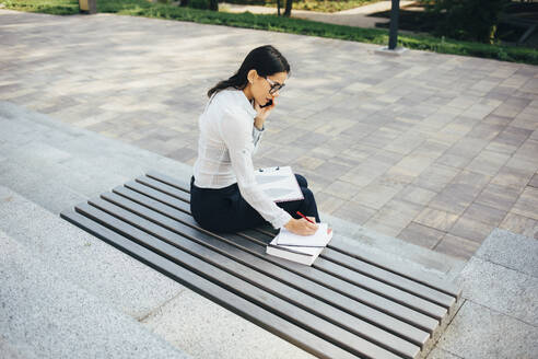 Young businesswoman sitting on a bench talking on cell phone and taking notes - OYF00034