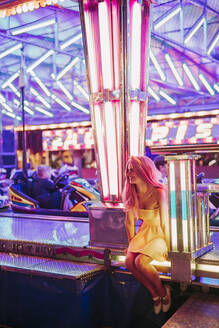 Happy young woman sitting at the bumper car on a funfair at night - LJF00885