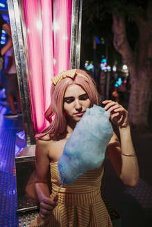 Portrait of a young woman with cotton candy on a funfair at night - LJF00900
