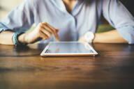 Woman sitting in a cafe using a digital tablet - OYF00050