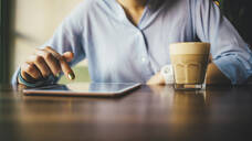 Woman sitting in a cafe using a digital tablet and drinking a coffee - OYF00053