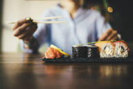 Close-up of a woman eating sushi in a restaurant - OYF00056
