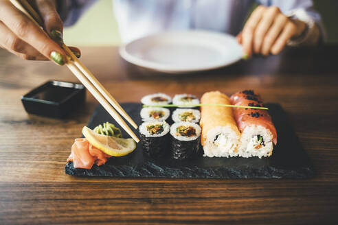 Close-up of a woman eating sushi in a restaurant - OYF00059