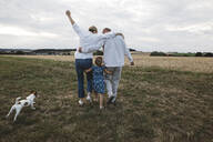 Rear view of family with dog walking on a meadow - KMKF01052
