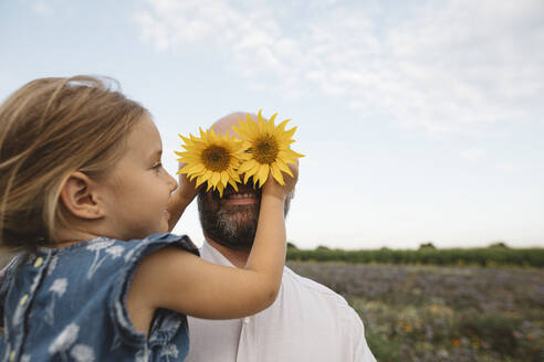 Daughter covering eyes of father with sunflowers - KMKF01055